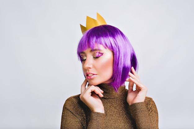 ゴールドクラウンの紫色の髪型と肖像画のきれいな女性。彼女は平和そうに見え、目を閉じてすみれ色の見掛け倒しをしています。 無料写真