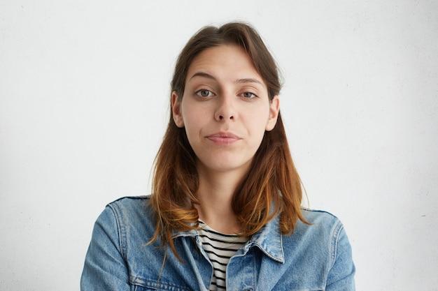 Ritratto di donna abbastanza giovane alzando il sopracciglio con meraviglia vestito con giacca di jeans isolato. donna sospettosa che aggrotta la fronte. Foto Gratuite