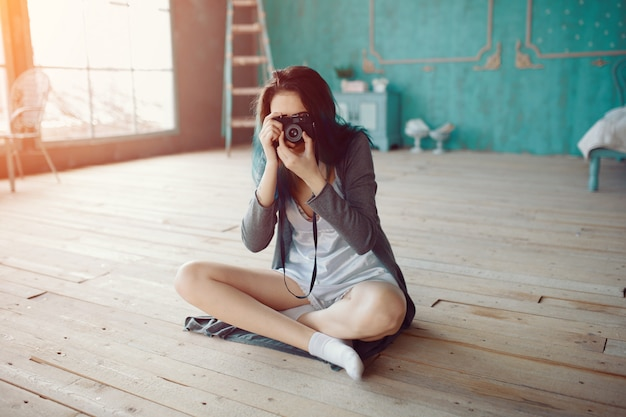 Portrait of pretty young girl taking picture on film camera Free Photo