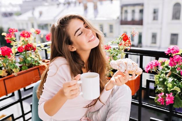 Ritratto piuttosto giovane ragazza con i capelli lunghi facendo colazione sul balcone al mattino. ha in mano una tazza, un cornetto, tiene gli occhi chiusi e sembra divertita. Foto Gratuite