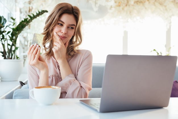Portrait of a pretty young woman holding goldern credit card Premium Photo