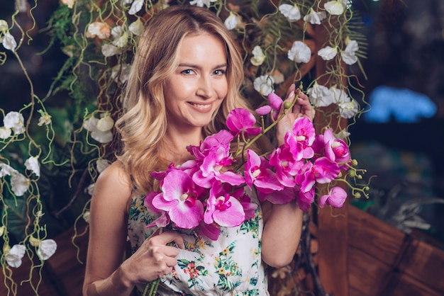 Portrait of pretty young woman holding pink orchids in hand Free Photo
