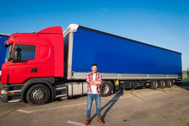 Ritratto di autista di camion americano professionista in abbigliamento casual e stivali in piedi davanti al veicolo camion con rimorchio lungo Foto Gratuite
