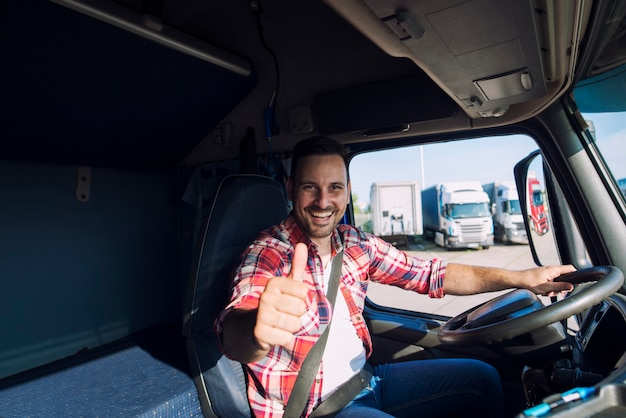 Portrait of professional motivated truck driver holding thumbs up in truck cabin Free Photo
