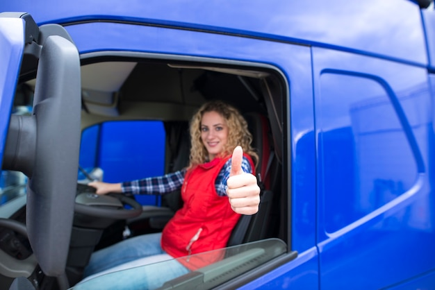 Portrait of professional truck driver showing thumbs up and smiling Free Photo