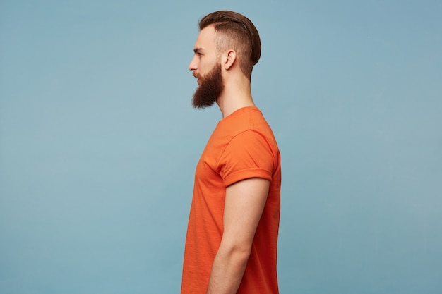 Portrait in profile of a guy with a fashionable hairstyle and a shaven head and a long thick beard in a red t-shirt standing sideways isolated on a blue Free Photo