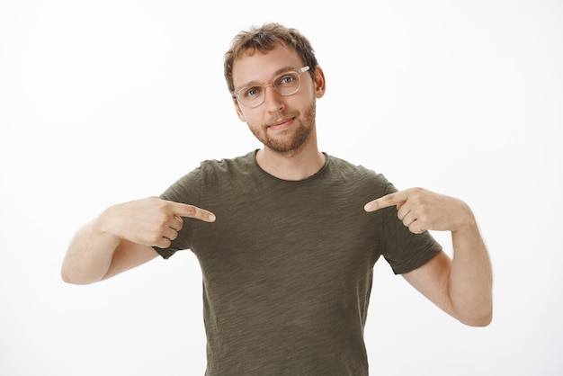 Portrait of proud and pleased self-assured handsome male entrepreneur in glasses and dark-green t-shirt pointing at himself and smiling bragging about own achievements Free Photo