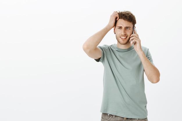 Ritratto di interrogato carino biondo uomo con setole, tenendo lo smartphone vicino all'orecchio e grattandosi la testa mentre si cerca di rispondere alla domanda, essendo incerti e dubbiosi Foto Gratuite