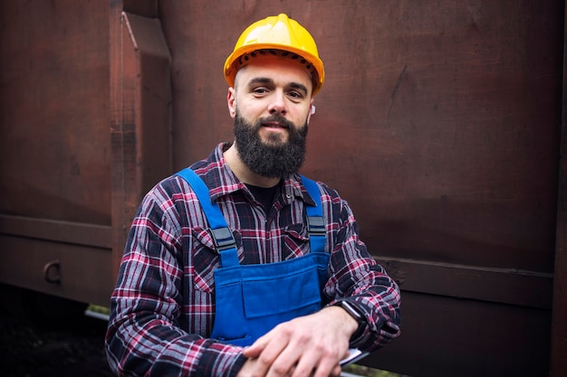 Portrait of railroad worker standing by train freight car Free Photo