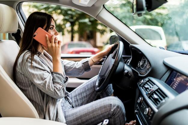 Ritratto di guidatore spericolato parlando con il suo telefono cellulare mentre si guida l'auto Foto Gratuite