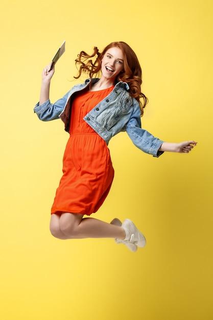 ポートレート、赤、髪、幸せ、若い、女、身に着けていること、旅行、パスポート、ジャンプ、 Premium写真