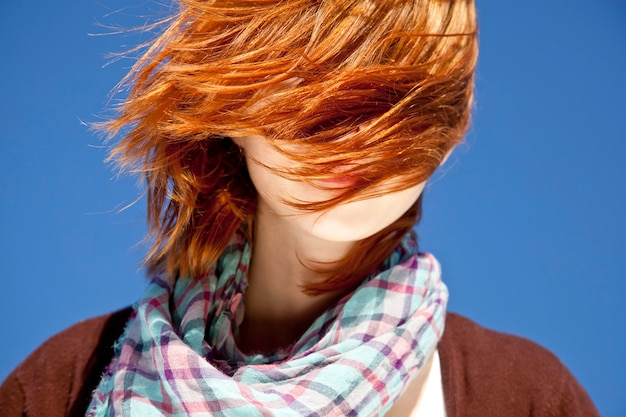 Portrait of red-haired girl with scarf on blue background. Premium Photo