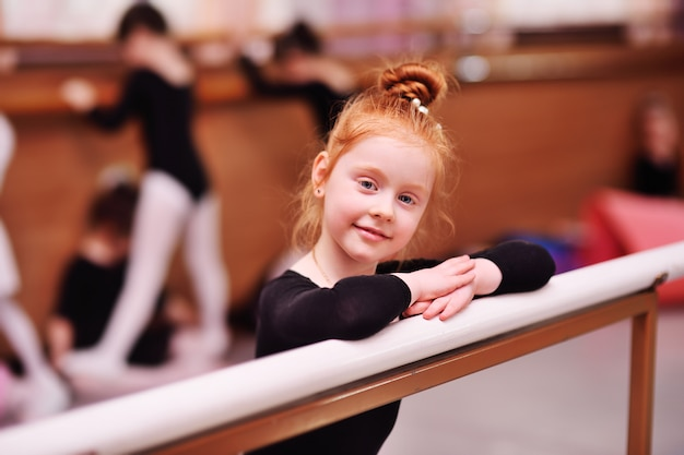 Portrait of a red-haired little girl ballerina at the ballet barre Premium Photo