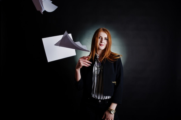 Portrait of a redheaded businesswoman in striped blouse and jacket throwing the paper away. Premium Photo
