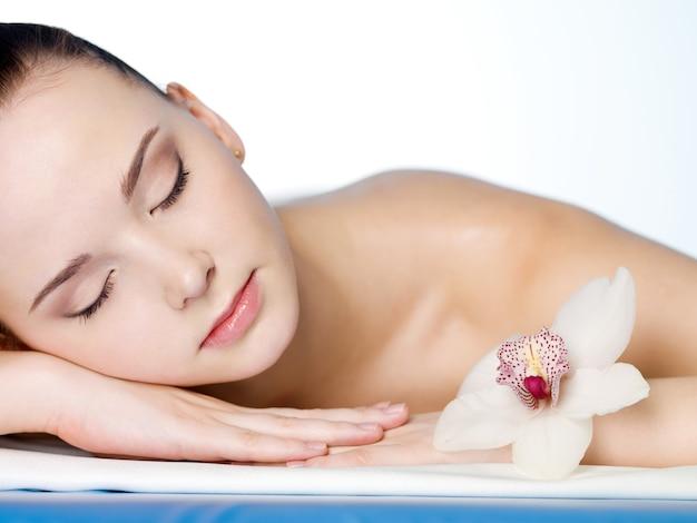 Ritratto di giovane bella donna di riposo nel salone della stazione termale di bellezza con il fiore Foto Gratuite