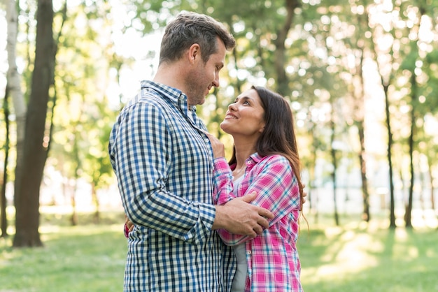 Portrait of romantic couple looking at each other while embracing in park Free Photo