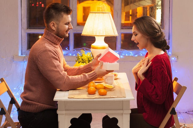 Portrait of romantic couple at valentine's day dinner with  gift Free Photo