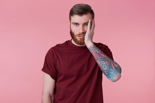 Ritratto di triste annoiato giovane con la mano tatuata, puntellando la testa, isolato su sfondo rosa. Foto Gratuite