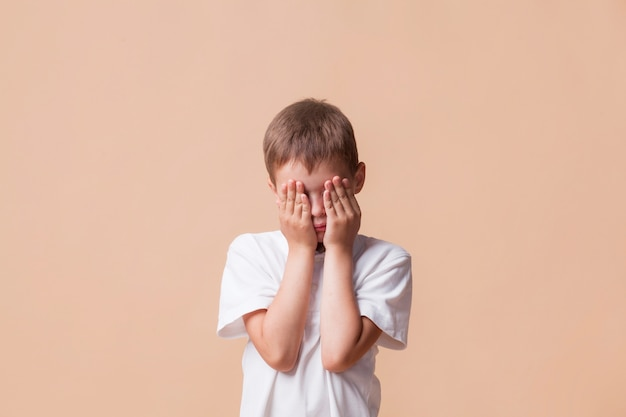 Portrait of sad boy covering his face with hand Free Photo