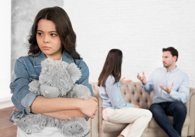 Portrait of sad child holding her teddy bear Free Photo