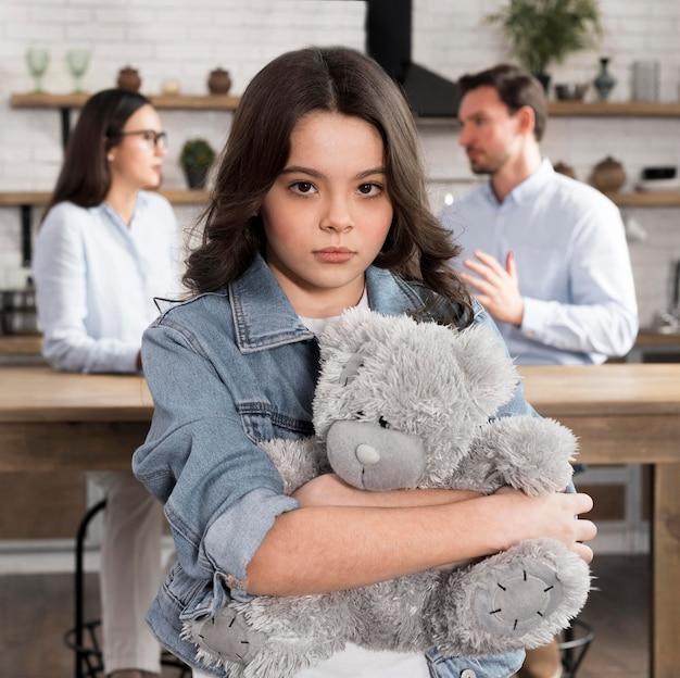 Portrait of sad daughter holding teddy bear Free Photo