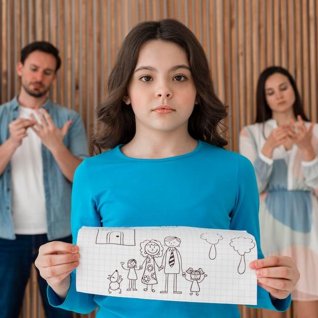 Portrait of sad girl holding family drawing Free Photo