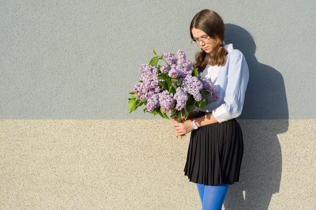 Portrait sad girl with bouquet of lilacs Premium Photo