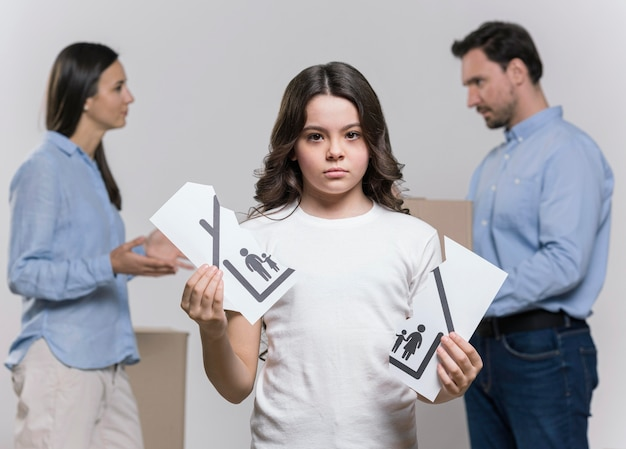 Portrait of sad girl with parents arguing behind Free Photo