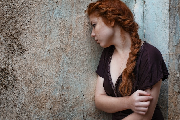 Portrait of a sad red-haired girl, sadness and melancholy in her eyes Premium Photo