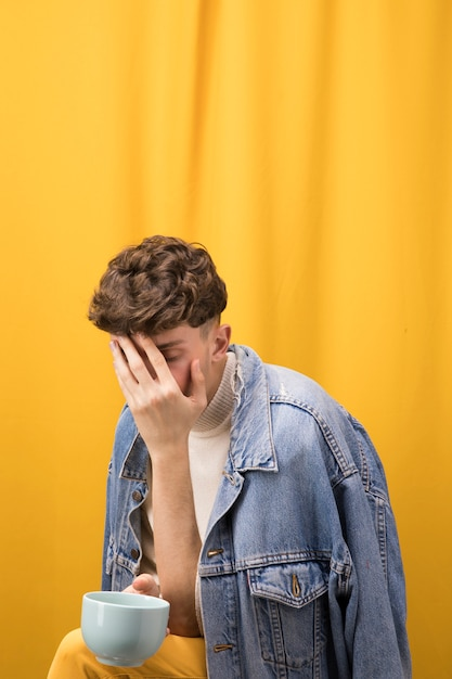 Portrait of sad young man in a yellow scene Free Photo
