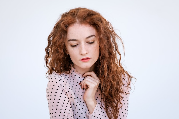 Portrait of a sad young woman with red hair close-up, downcast eyes on a light background Premium Photo