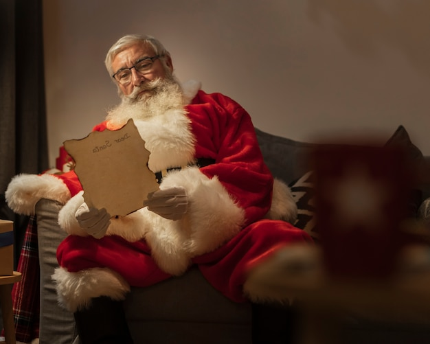 Portrait of santa claus reading christmas letter Free Photo