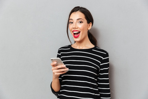 Portrait of a satisfied woman holding mobile phone Free Photo