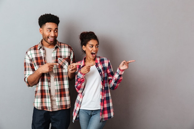 Portrait of a satisfied young african couple pointing side with fingers Free Photo
