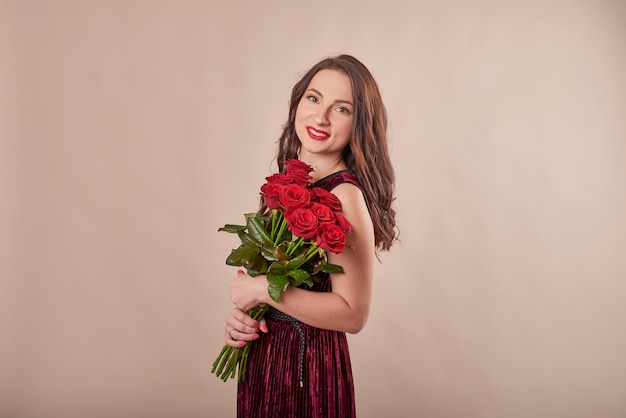 Portrait of satisfied young woman in red dress with bouquet of roses Premium Photo