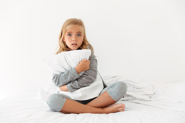 Portrait of a scared little girl hugging pillow Free Photo
