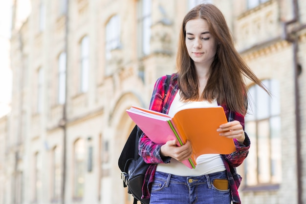 Portrait of school girl with book in city Free Photo