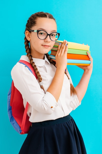 Portrait of a schoolgirl in glasses with books textbooks on yellow blue Premium Photo
