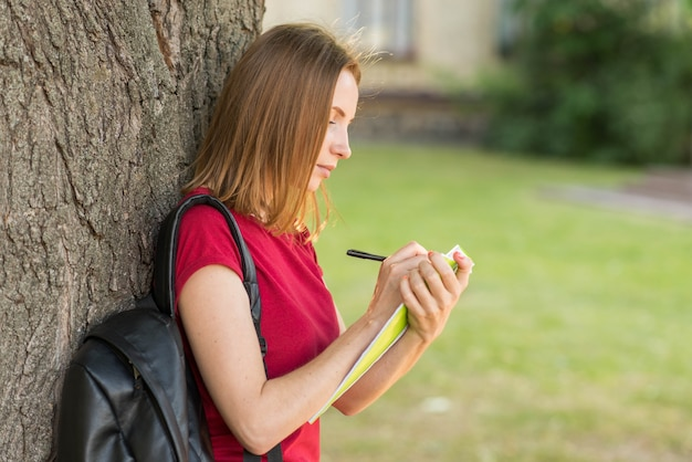 Portrait of schoolgirl leaning against tree Free Photo