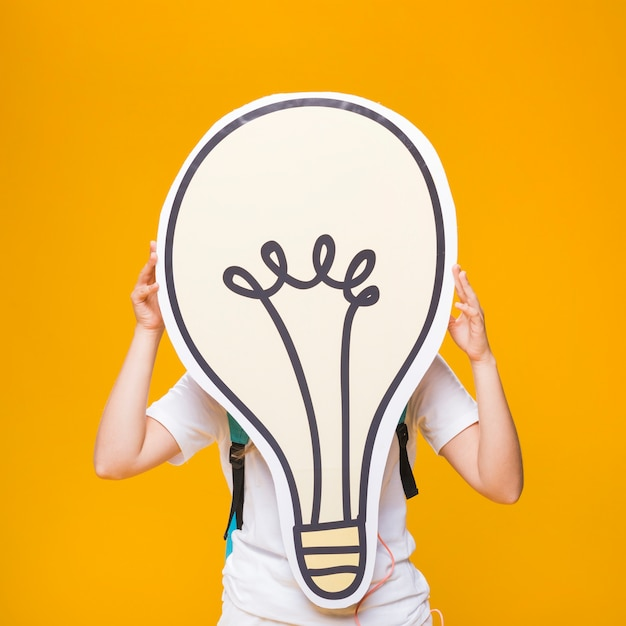 Portrait of schoolgirl with big light bulb Free Photo