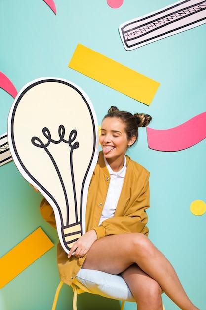 Portrait of schoolgirl with big light bulb Free Photo