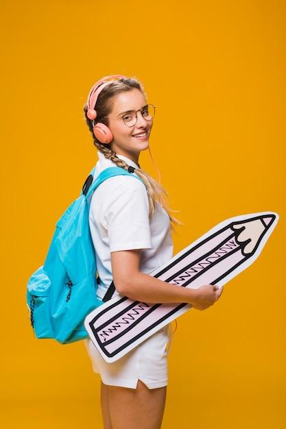 Portrait of schoolgirl on yellow background Free Photo