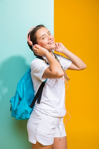 Portrait of schoolgirl on yellow and blue background Free Photo