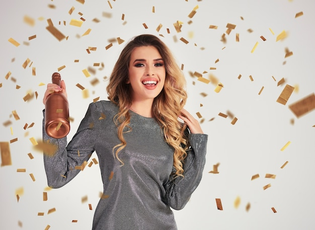 Portrait of screaming woman holding a bottle of champagne Free Photo
