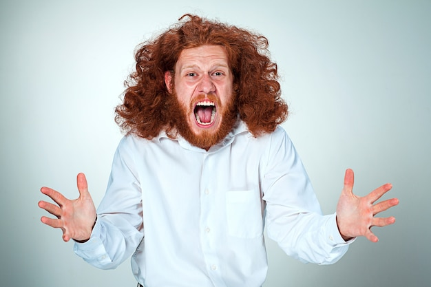 Portrait of screaming young man with long red hair and shocked facial expression on gray wall Free Photo