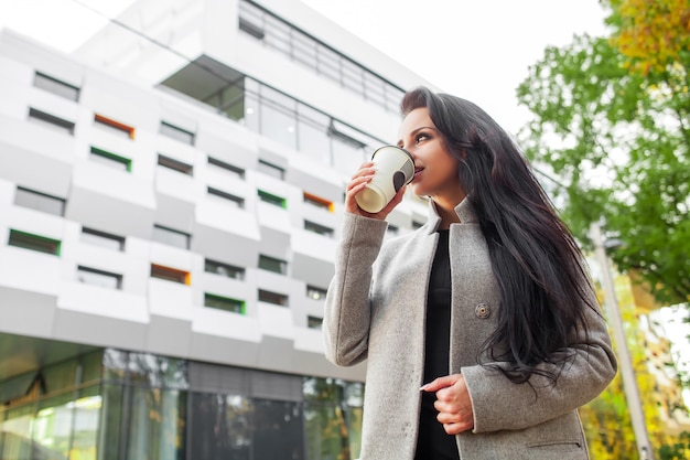 Portrait of self confidence business woman with coffee to go next to the office. Premium Photo