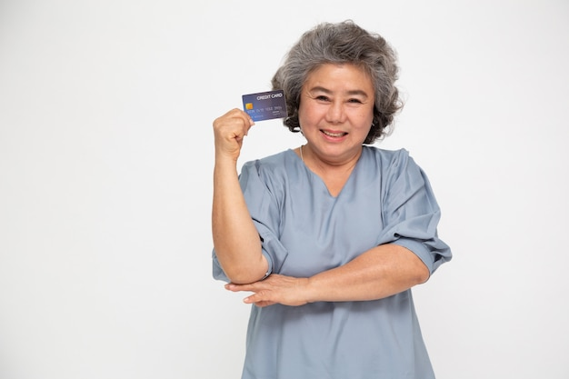 Portrait of senior asian woman holding credit card and showing on hand Premium Photo
