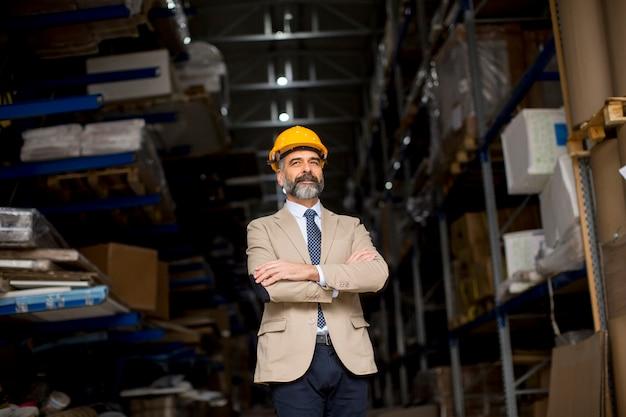 Portrait of senior businessman in suit with helmet in a warehouse Premium Photo