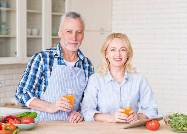 Portrait of a senior couple holding glass of juice with digital tablet and vegetable on wooden table Free Photo