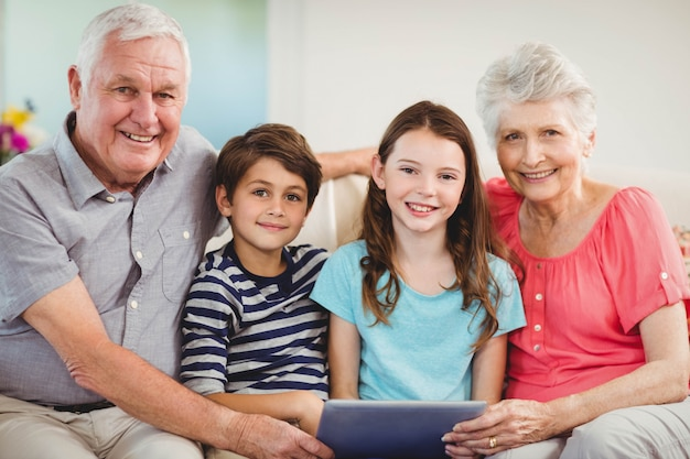 Portrait of senior couple and their grand children using digital tablet in living room Premium Photo